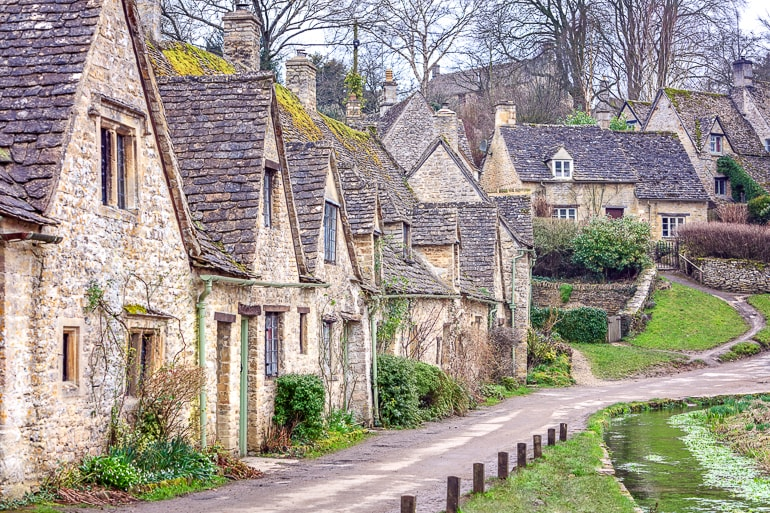 grey stone cottages with walking path in village in cotswolds