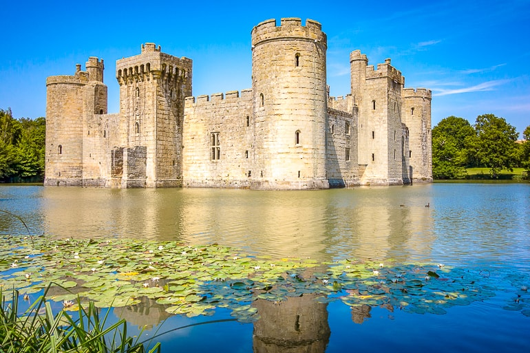 large castle with moat in front reflecting off water bodiam castle