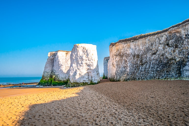 white stone cliffs with beach below and blue sky behind in botany bay