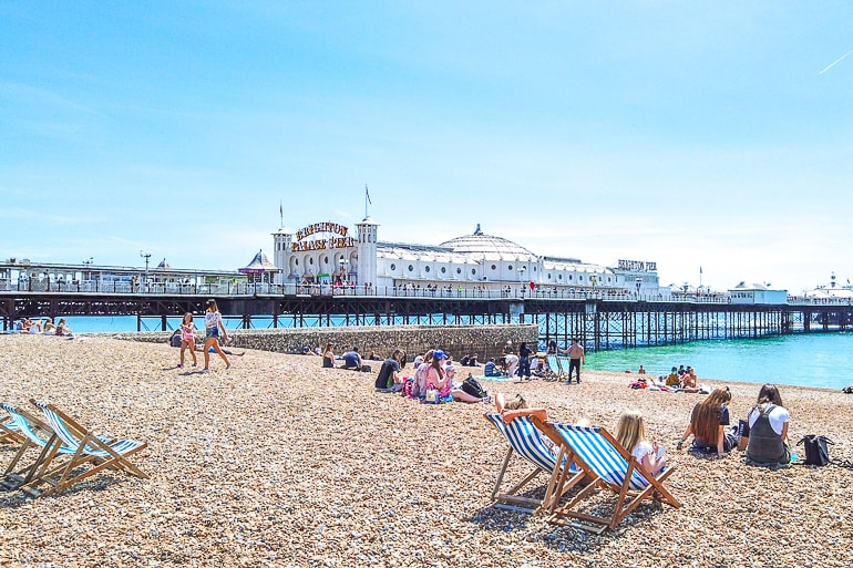 long ocean pier with white building and rock beach in front in brighton day trip from london