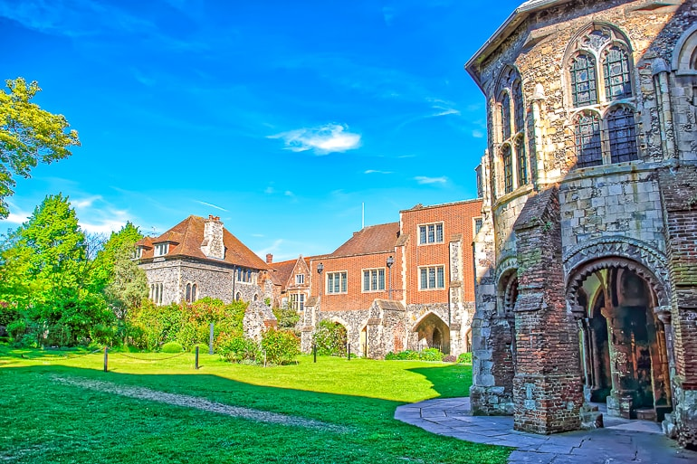 stone abbey with houses behind and green gardens in canterbury day trips from london