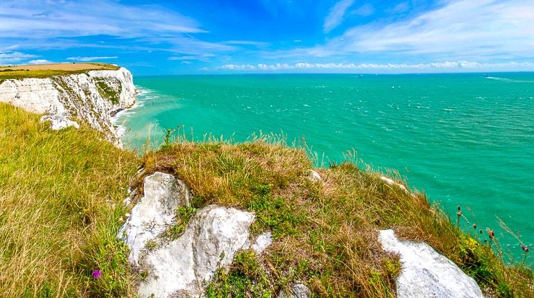 blue water below white cliffs covered in green grass