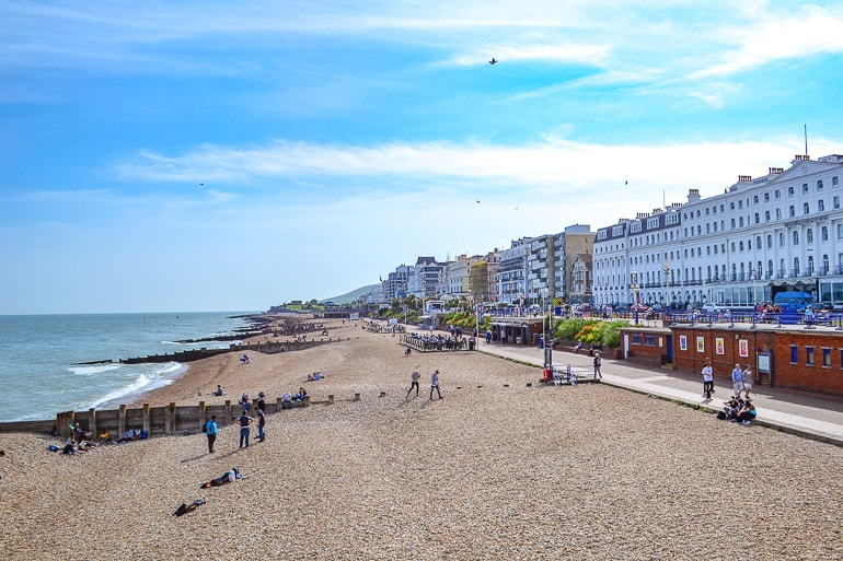 stone beach with city buildings and boardwalk in distance in eastbourne uk