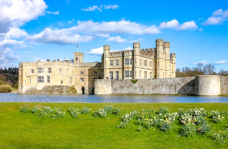 large castle with water around and green grass in front leeds castle