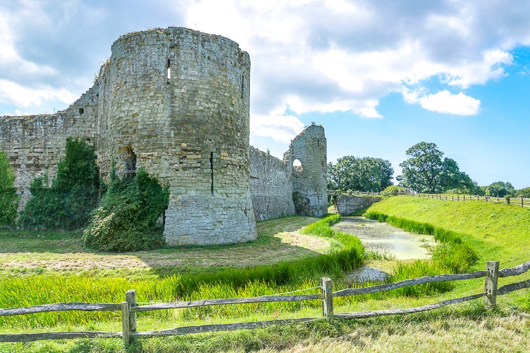 green grass around stone castle ruins at pevensey castle