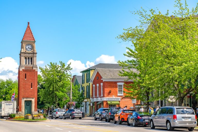 cars parked along street with red brick clock tower in road day trips from toronto niagara on the lake