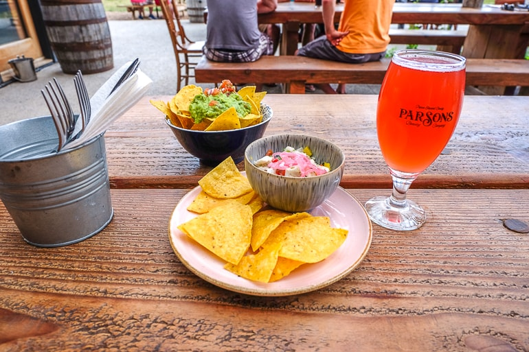 chips and salsa on plate with pint of beer on wooden table at parsons brewery prince edward county toronto day trip