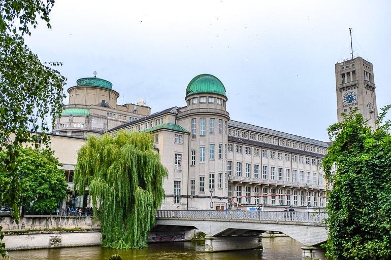 Weißes Museumsgebäude mit grüner Kuppel und Bäumen im Vordergrund