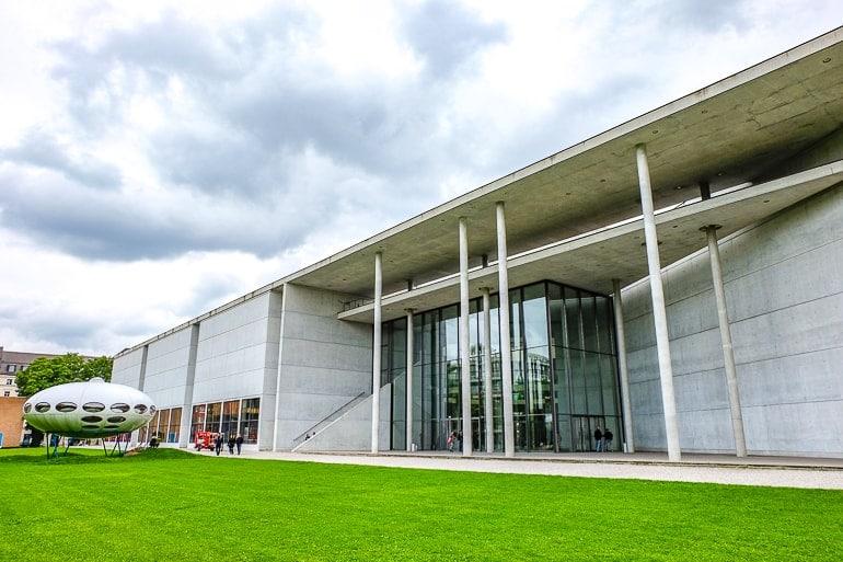 Silberfarbenes modernes Museum mit Ufo vor Eingang und grünem Gras