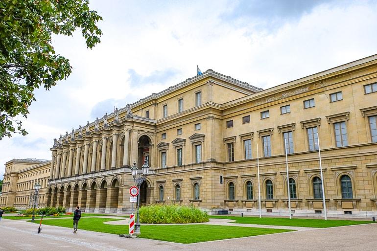 Gelbes Gebäude Residenz mit Bäumen und grünem Gras im Vordergrund