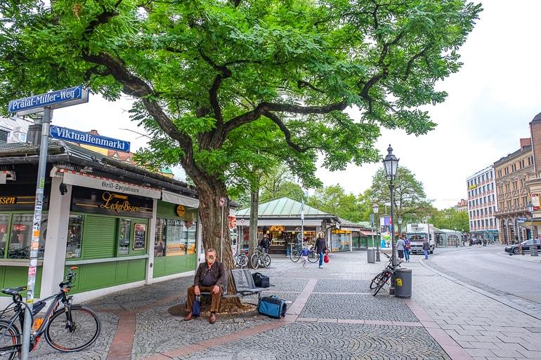 Mann sitzt neben Baum mit geschlossenen Marktständen im Hintergrund München Viktualienmarkt