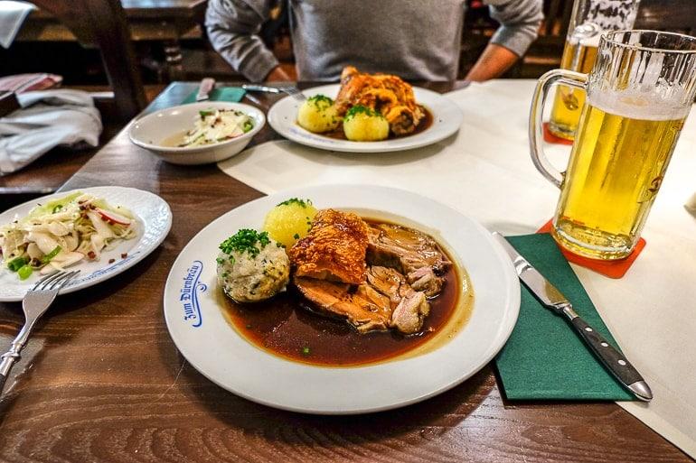 Zwei Teller mit Knödeln und Fleisch neben Bier auf Tisch in Restaurant