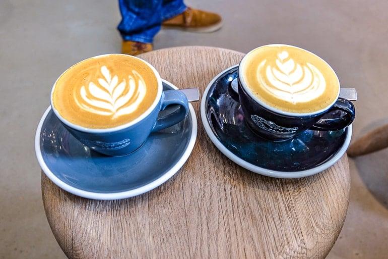 Zwei Kaffees mit Latte-Kunst auf Holzstuhl in Cafe in München