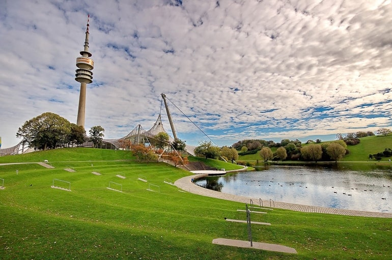 tv tower standing over green lawn and pond in olympic park one day in munich
