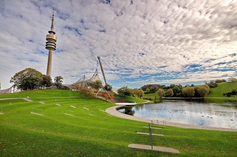 Fernsehturm über grünem Gras und Teich im Olympiapark in München