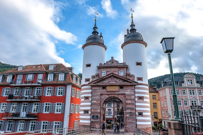 old gate with white towers and archway at end of bridge heidelberg germany
