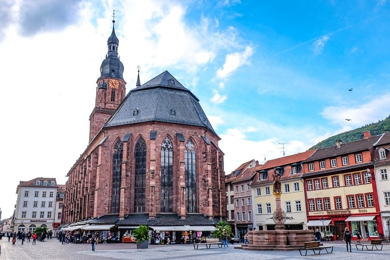 red church with tower in old market square in heidelberg germany things to do