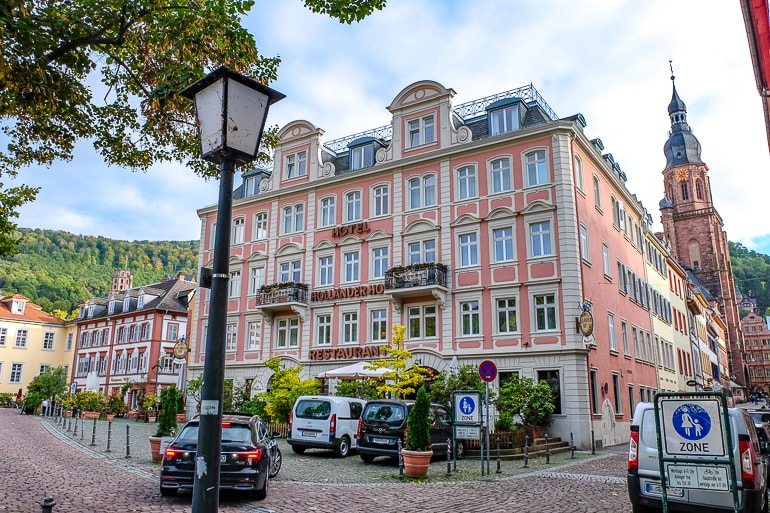 pink hotel exterior with cars parked in front heidelberg germany