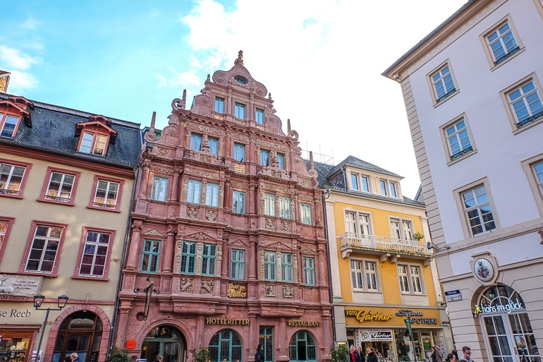 red hotel exterior with old town buildings beside in heidelberg germany
