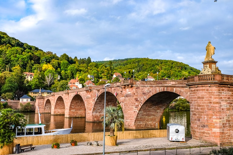 red arch bridge over river with green trees behind heidelberg germany