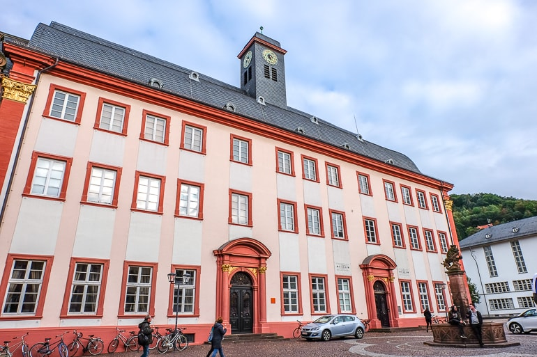 red and white old university building with clock in old town heidelberg germany