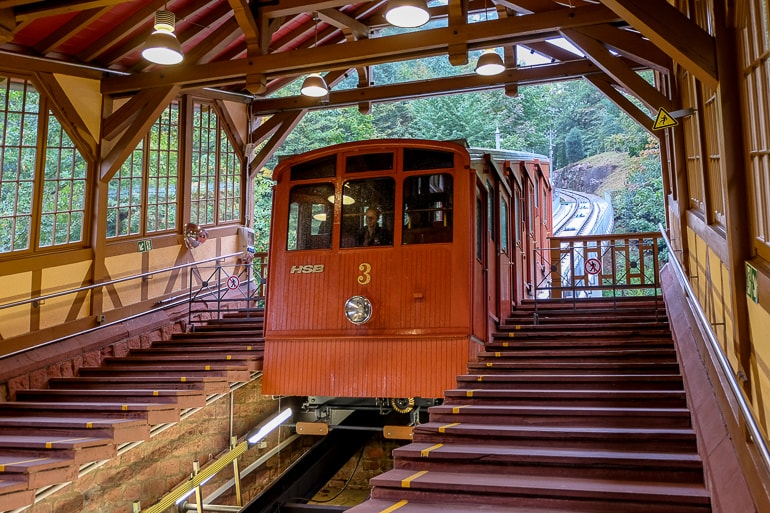 red cable tram car under wooden station roof in heidelberg germany