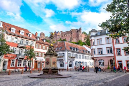 colourful old town square with fountain and castle behind things to do in heidelberg germany