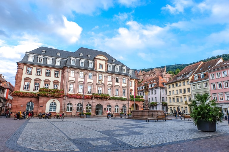open square with fountain and town hall behind in heidelberg germany