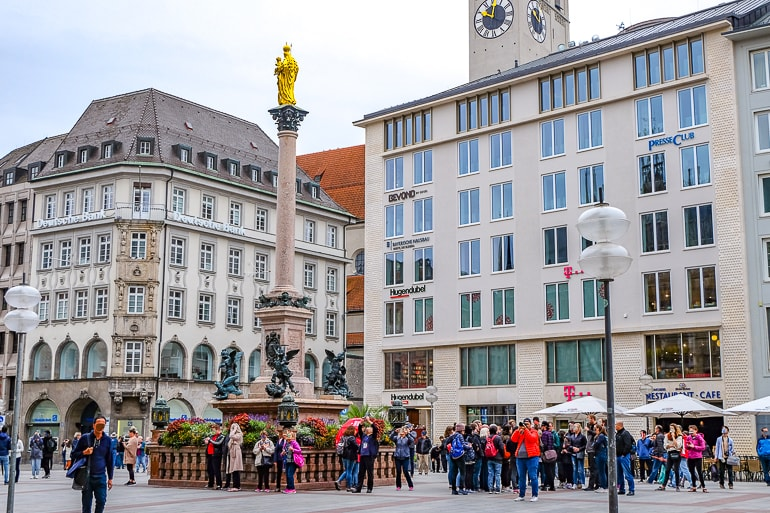 hotel buildings behind people standing in market square marienplatz munich