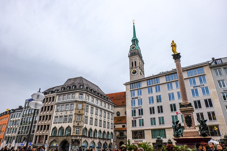hotel buildings with church clock tower behind and small fountain where to stay in munich old town