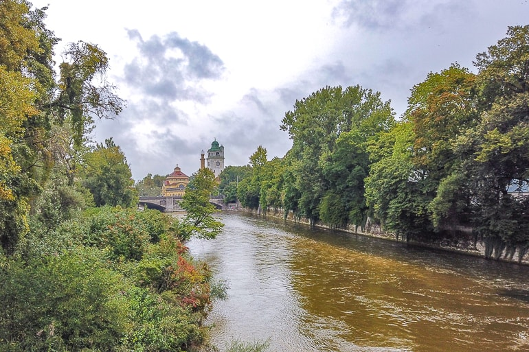 green trees lining brown river in munich with buildings behind