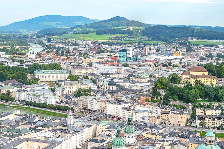 city buildings from above with green hills behind in salzburg austria