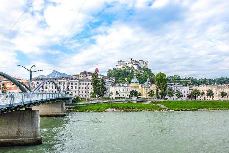 castle on hill overlooking river with bridge across it old town salzburg austria