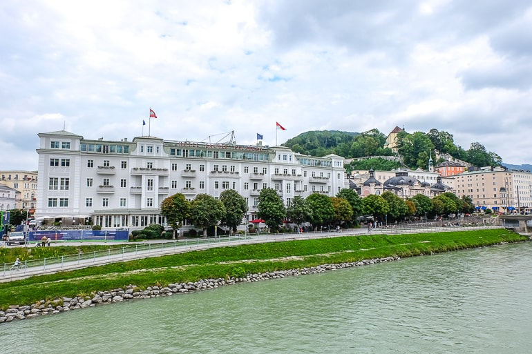 white hotel in city sitting along green river bank where to stay in salzburg austria