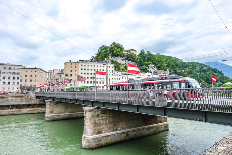 red tram crossing bridge over river with old town buildings behind salzburg austria