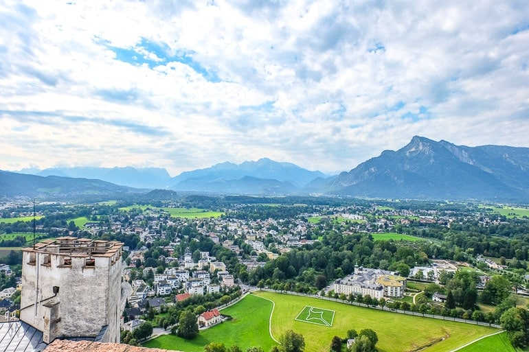 green field with houses beside and mountain in distance nonntal neighbourhood salzburg austria