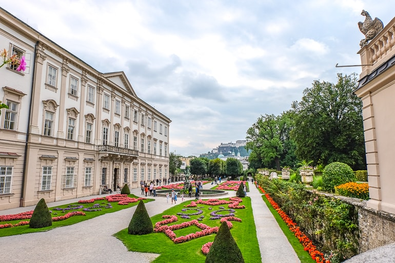 green and red gardens with paths and historic building in mirabell palace salzburg austria where to stay