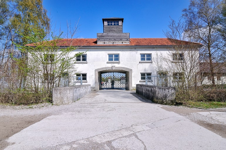 white gatehouse building with laneway and trees at dachau munich