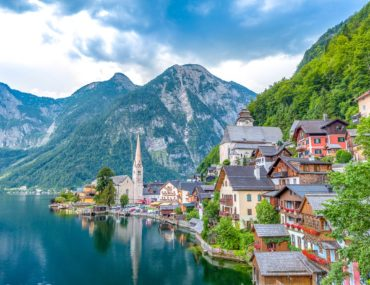village by lake with mountains behind day trips from salzburg