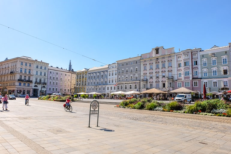 pastel buildings on city square with cafes and people walking in linz austria