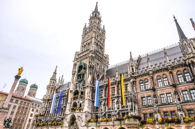 tall clock tower of munich town hall with flags