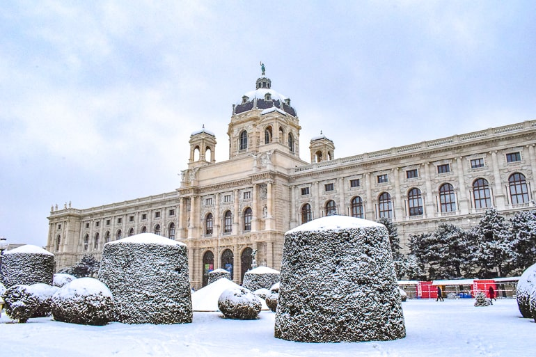 beige museum building with green dome covered in snow vienna austria day trip from salzburg