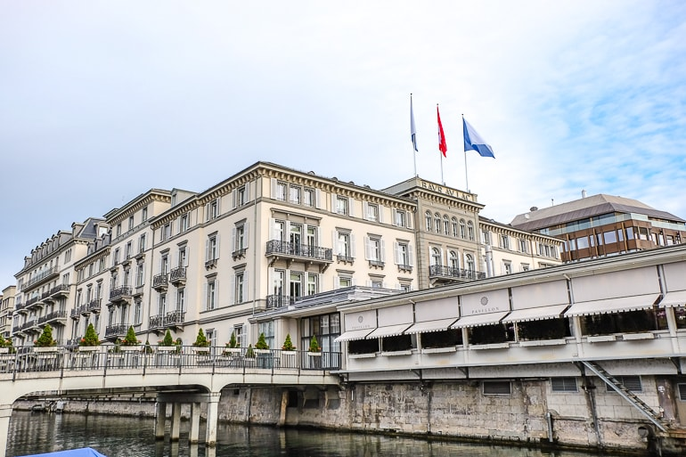 large fancy hotel with flags and river beside luxury hotel zurich