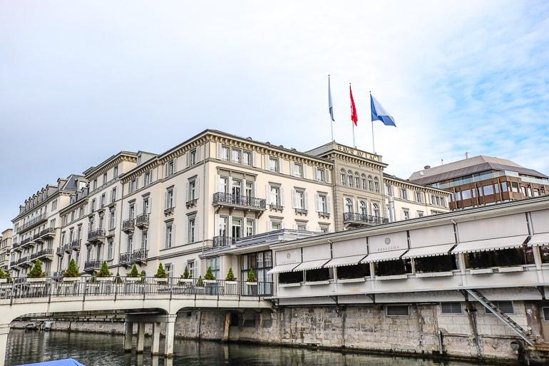 Großes Hotel mit Flaggen und Fluss daneben Luxushotel Zürich