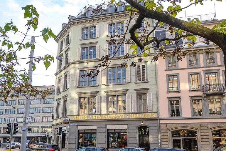 Beiges Hotel mit ungewöhnlichen Fenstern an Straße