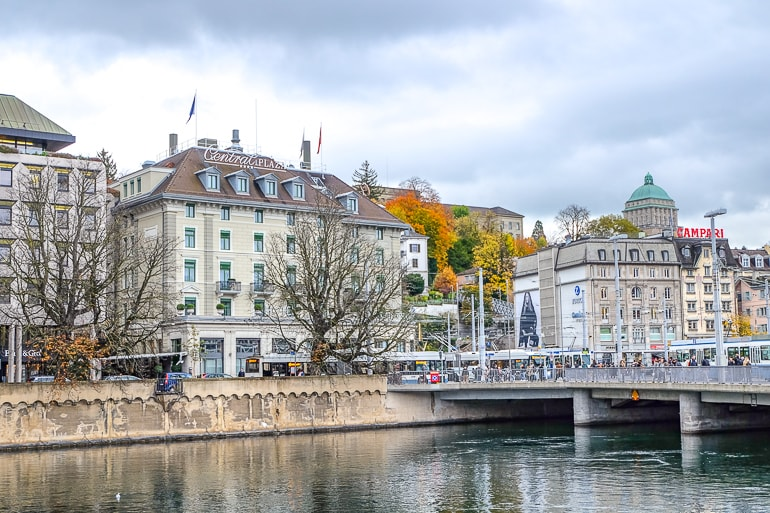 hotel on river bank with bridge in front and city behind zurich