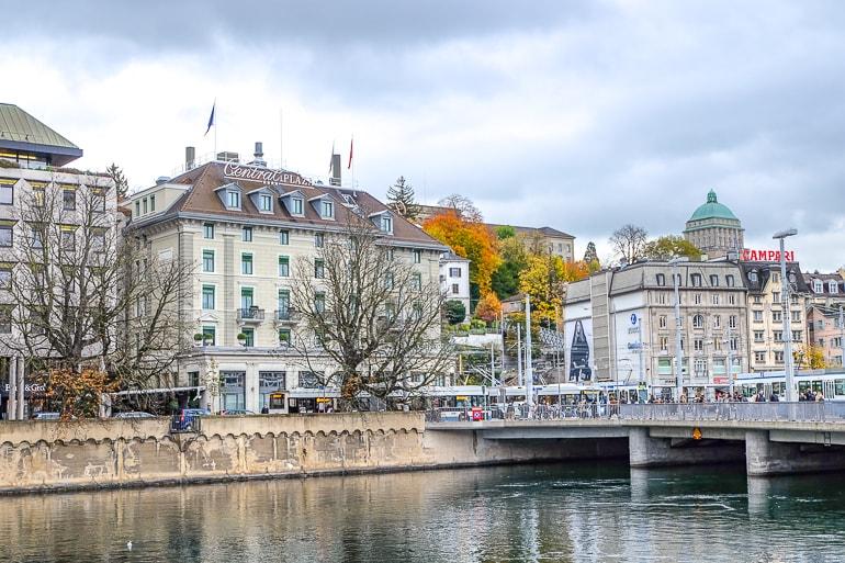 Hotel am Flussufer mit Brücke im Vordergrund und anderen Gebäuden