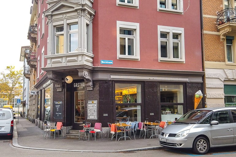 Kleines Cafe an Straßenecke mit Gasthaus im Haus und Autos vor Gebäude Zürich Unterkunft