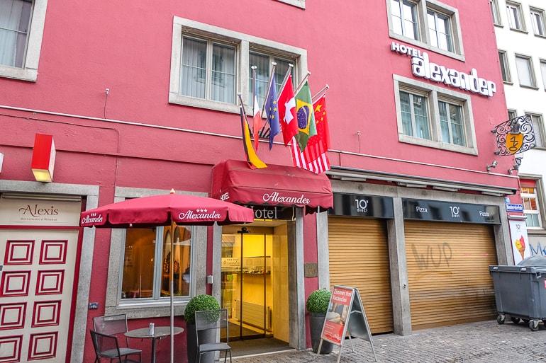 Rote Fassade von Hotel mit hängenden Flaggen über Eingang
