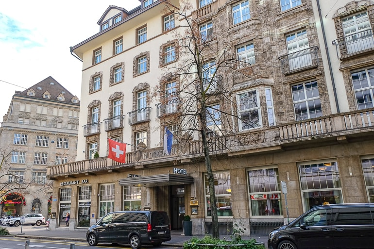 fancy hotel with swiss flag hanging out front and cars parked on street